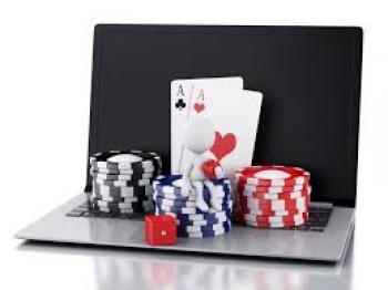 Laptop med spelmarker, spelkort, tärningar och en vit figur